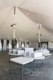 Inside a large white tent for entertaining. A large white tent iwith tables and chairs for parties and enteraining Royalty Free Stock Image