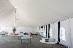 Inside a large white tent for entertaining. A large white tent iwith tables and chairs for parties and enteraining Stock Photography