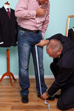 Inside leg measured by a tailor for a suit. Photo of a men having his inside leg measured by a tailor during a bespoke suit fitting Stock Image