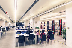 Library. Interior of library hall at night. People in reading study room. Reader studying on desk Royalty Free Stock Images