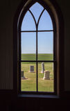 Inside looking out of arched church window looking at grave yard. Stock Photo