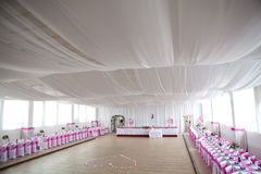 The inside of a massive white wedding tent with ta. Bles and chairs already in position, day light royalty free stock photo