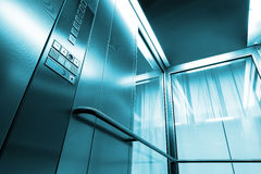 Inside metal and glass Elevator in modern building , the shiny buttons and railings Royalty Free Stock Images