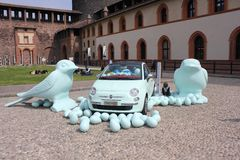 Inside the Milan Sforza Castle, plastic birds on the floor with a Fiat 500 car Stock Photo