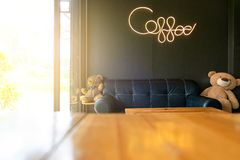 "Inside modern coffee shop decorative black sofa and wooden tables and ""coffee"" word writing with neon light. On black wall background royalty free stock photo"