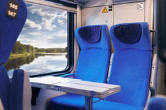 Inside of modern express train. Nobody in blue chairs at window. Comfortable chairs and table in foreground, nature outside window Stock Photography