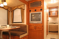 Inside a motor home. Interior of motor home with dining table and dishes, tv, covered windows, and bedroom showing Royalty Free Stock Photo