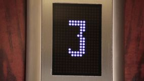 Inside moving up elevator, close up of a digital display showing floor number and arrow in white. Close up stock video footage