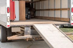 Inside a moving van with a ramp for easy access. Inside of a moving van partially loaded with furniture, and a ramp to make loading easier stock photo