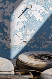 Inside An Old Abandoned Industrial Building, Factory. The Wall With Peeling Blue Paint. Used Tires, Wheels. Many Different Garbage Stock Photos