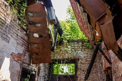 Inside an old brick house with a collapsed roof after a fire, thickets on the walls stock photos