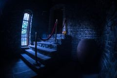 Inside of old creepy abandoned mansion. Staircase and colonnade. Halloween pumpkin on dark castle stairs to the basement. Spooky dungeon stone stairs in old stock image