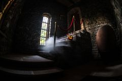 Inside of old creepy abandoned mansion. Staircase and colonnade. Halloween pumpkin on dark castle stairs to the basement. Spooky dungeon stone stairs in old stock photography