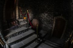 Inside of old creepy abandoned mansion. Staircase and colonnade. Halloween pumpkin on dark castle stairs to the basement. Spooky dungeon stone stairs in old royalty free stock photo