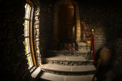 Inside of old creepy abandoned mansion. Staircase and colonnade. Halloween pumpkin on dark castle stairs to the basement. Spooky dungeon stone stairs in old royalty free stock images