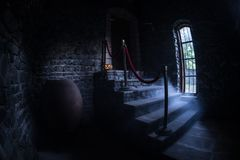 Inside of old creepy abandoned mansion. Staircase and colonnade. Halloween pumpkin on dark castle stairs to the basement. Spooky dungeon stone stairs in old stock images