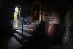 Inside of old creepy abandoned mansion. Staircase and colonnade. Halloween pumpkin on dark castle stairs to the basement. Spooky dungeon stone stairs in old royalty free stock image