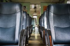 Inside of railway train with seats vintage style. Inside of old public Thai railway train cabin with seats, handrails, fan and interior in vintage style service stock photography