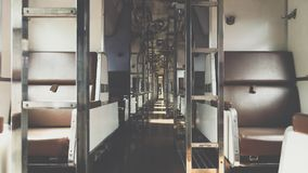 Inside of railway train with seats vintage style. Inside of old public Thai railway train cabin with seats, handrails, fan and interior in vintage style service stock photo