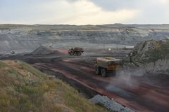 Inside of an open pit coal mine, large water trucks are spraying water on roads to control dust royalty free stock image