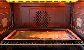 Inside The oven. A close view inside a  hot operational household oven with an empty tanished baking tray - 3D render Stock Photo