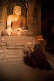 Inside pagoda novice is praying to the buddha. BAGAN, MYANMAR : Inside pagoda novice is praying to the buddha.Near the Bagan pagodas field. Rural landscape and royalty free stock image