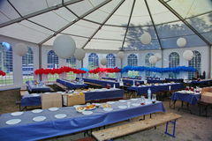 Inside a party tent. Inside view of a party events wedding celebration banquet tent. Empty marque set up with tables and chairs for wedding reception party with Stock Image