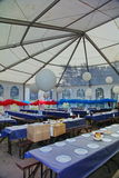 Inside a party tent. Inside view of a party events wedding celebration banquet tent. Empty marque set up with tables and chairs for wedding reception party with Royalty Free Stock Images