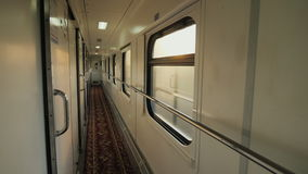 Inside the passenger railway car. The train rides fast, the morning sun shines through the windows. Static shot stock footage