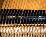 Inside of a piano with little hammer and strings Royalty Free Stock Image