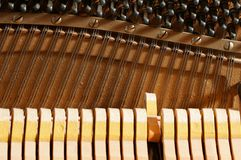 Inside a Piano - Strings. One hammer striking the strings inside a piano Royalty Free Stock Photography