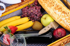 Inside A Picnic Basket. Closeup of the contents of a picnic basket these include red wine, grapes, red and green apples, kiwi fruit, bananas, strawberries and a Royalty Free Stock Images
