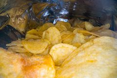 Inside the potato chips bag. Opened pack of original taste delicious potato crisps. Fast food and unhealthy eating concept.  royalty free stock images
