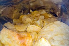 Inside the potato chips bag. Opened pack of original taste delicious potato crisps. Fast food and unhealthy eating concept.  royalty free stock photo