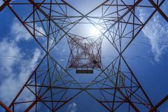 Inside of a power pylon and look into the sun Stock Photography