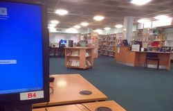 Inside a public library with computer and books. Stock Photos
