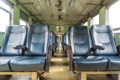 Inside of railway train with seats vintage style. Inside of old public Thai railway train cabin with seats, handrails, fan and interior in vintage style service royalty free stock photography