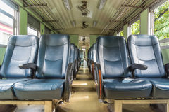 Inside of railway train with seats vintage style. Inside of old public Thai railway train cabin with seats, handrails, fan and interior in vintage style service stock images