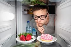 Man choosing between fruits and candy Royalty Free Stock Image