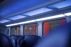 Inside a regional train, blurred abstract background in blue and. Inside a regional train without passengers, blurred abstract background in blue and red, small Stock Images