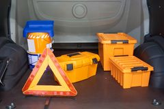 Inside repairman`s car. Paint, three orange toolboxes and road warning triangle Royalty Free Stock Images