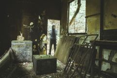 Inside a ruined hut in the middle of a forest with a spooky, blurred, ghostly figure standing inthe doorway, with a grunge muted e. Inside a ruined hut in the stock photo