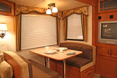 Inside RV - dining. Interior of a motor home showing dining table with dishes, TV, remotes, covered windows Stock Image