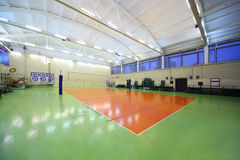 Inside school gym hall and volleyball net. Inside lighted school gym hall with green-orange floor and volleyball net royalty free stock photography