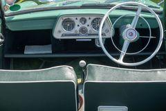 Inside of a Singer car. Dashboard and steering wheel of a convertible English Singer car, showing the dials and speedo with the front seats. Taken at a vintage Royalty Free Stock Images