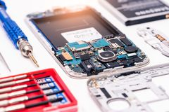 The inside of the smartphone`s motherboard and tools lay on the back table. the concept of computer hardware, mobile phone, electr stock images