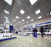 Inside spacious shoes shop with models on shelves Royalty Free Stock Photography
