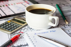 Inside the Stock Exchange, business plan, what to do. Coffee cup and pen with notebook on the desk Stock Image