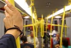 Inside the subway car with the commuter's hand Stock Photo