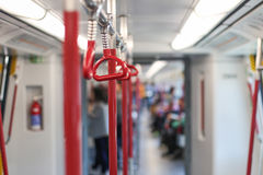 Inside the subway car. Red handrails in the subway. White light Royalty Free Stock Photo